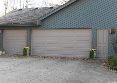 Sandstone Tan Long Panel Garage Doors matching entry Door